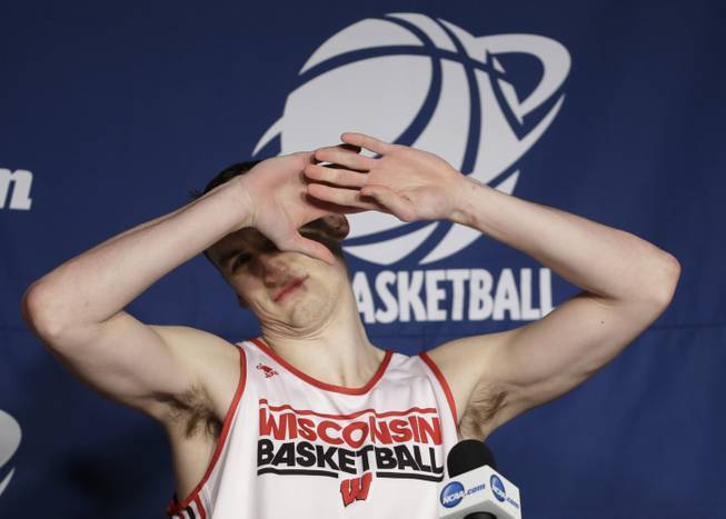 Wisconsin forward Sam Dekker reacts to the lights as he arrives at a news conference for the third-round game of the NCAA college basketball tournament Friday, March 21, 2014, in Milwaukee. Wisconsin plays Oregon on Saturday.