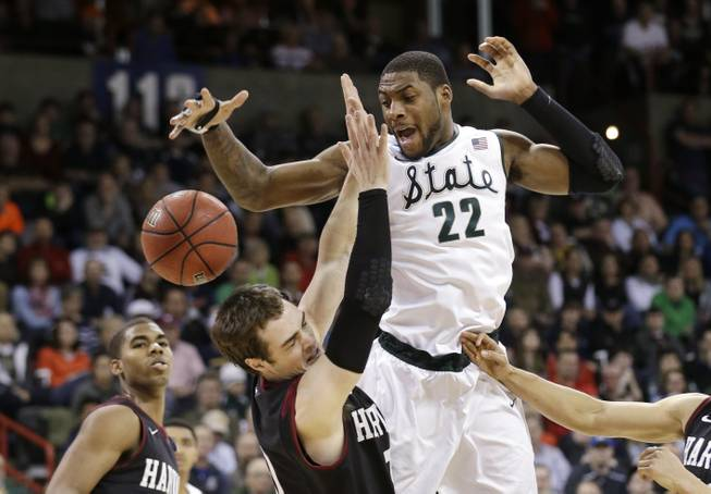 Michigan State's Branden Dawson (22) and Harvard's Laurent Rivard go for a loose ball in the second half during the third round of the NCAA men's college basketball tournament in Spokane, Wash., Saturday, March 22, 2014. Michigan State won 80-73.