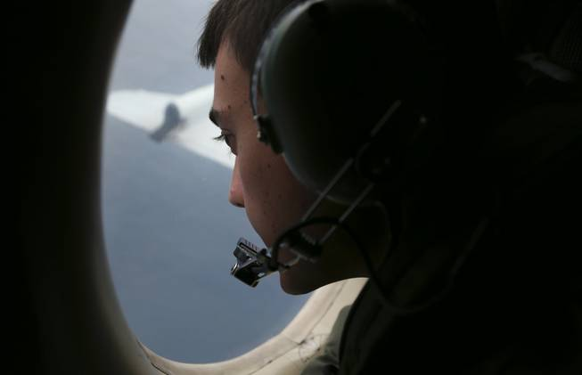Sgt. Matthew Falanga, onboard a Royal Australian Air Force AP-3C Orion, searches for the missing Malaysia Airlines Flight 370 in the southern Indian Ocean off Australia on Saturday, March 22, 2014.