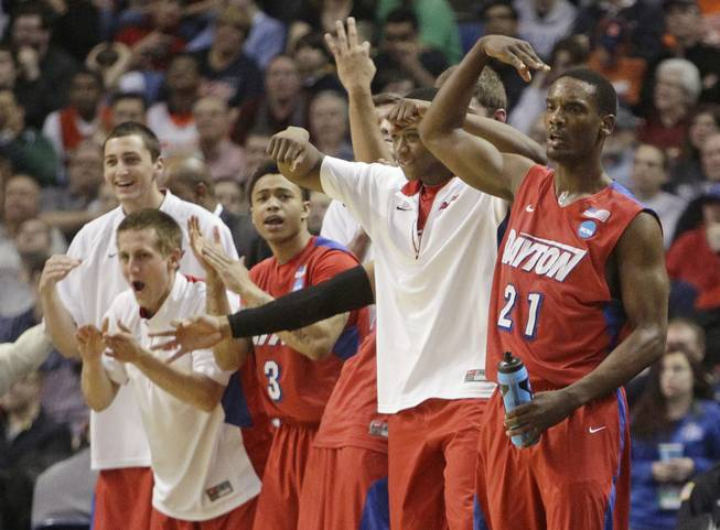 Dayton's Dyshawn Pierre (21) celebrates with teammates during the second half of a third-round game against Syracuse in the NCAA men's college basketball tournament Saturday, March 22, 2014, in Buffalo, N.Y.