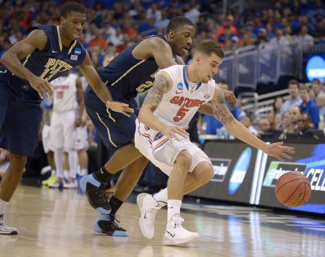 Florida guard Scottie Wilbekin (5) forces Pittsburgh forward Lamar Patterson (21) to turn over the ball as Pittsburgh guard Josh Newkirk (13) closes in during the second half in a third-round game in the NCAA college basketball tournament Saturday, March 22, 2014, in Orlando, Fla.