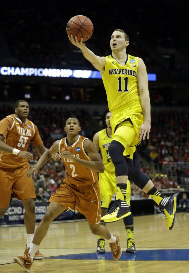 Michigan guard Nik Stauskas drives to the basket during the first half of a third-round game against Texas in the NCAA college basketball tournament Saturday, March 22, 2014, in Milwaukee.