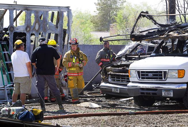 Clark Country Firefighters mop up after a backyard blaze that started in a recreational vehicle near East Windmill Avenue and Bermuda Road Sunday, March 23, 2014. Two RV's, a shed and a trailer were destroyed but there were no injuries reported in the fire.