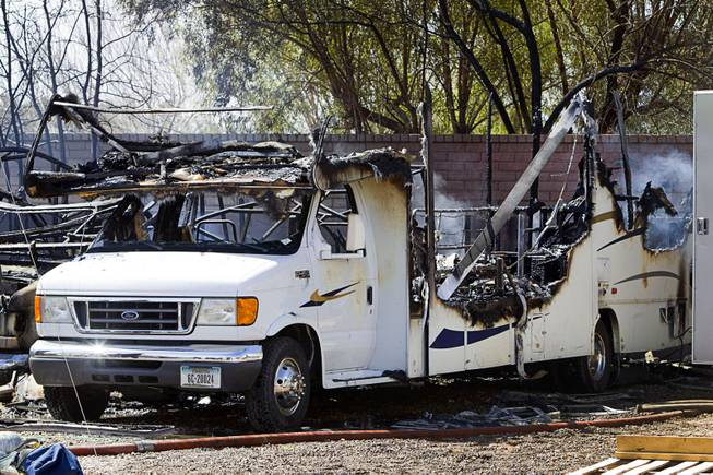 A destroyed recreational vehicle is shown after a fire near East Windmill Avenue and Bermuda Road Sunday, March 23, 2014. Homeowner Gary Baxter said he and others were working in the backyard when they noticed smoke coming from a smaller RV (left of the pictured RV). They tried to move the larger RV but it had been sitting unused for a while and the battery was dead. Two RV's, a shed and a trailer were destroyed but there were no injuries reported.