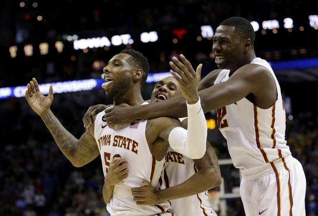 Iowa State's DeAndre Kane (50) is grabbed by teammates Monte Morris, center, and Daniel Edozie, right, after making the game-winning basket against North Carolina during the second half of a third-round game in the NCAA college basketball tournament Sunday, March 23, 2014, in San Antonio. Iowa State won 85-83.