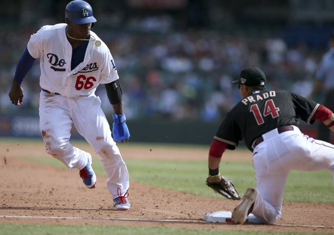 Los Angeles Dodgers' Yasiel Puig, left, is about to be tagged out at third base by the Arizona Diamondbacks' Marin Prado during the second game of the two-game Major League Baseball opening series between the two teams at the Sydney Cricket ground in Sydney on Sunday, March 23, 2014.