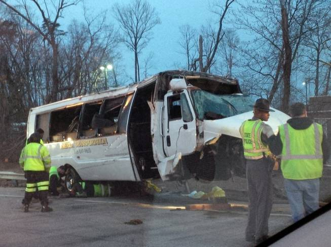 Police investigate the scene of a bus accident on Interstate 95 early Sunday, March 23, 2014, in Fairfax County, Va. The shuttle bus struck a guardrail and overturned before dawn Sunday just south of the nation's capital, leaving at least one person dead and sending 16 others to the hospital, Virginia State Police said.