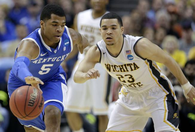 Kentucky guard Andrew Harrison (5) and Wichita State guard Fred VanVleet (23) go for a loose ball during the first half of a third-round game of the NCAA college basketball tournament Sunday, March 23, 2014, in St. Louis.