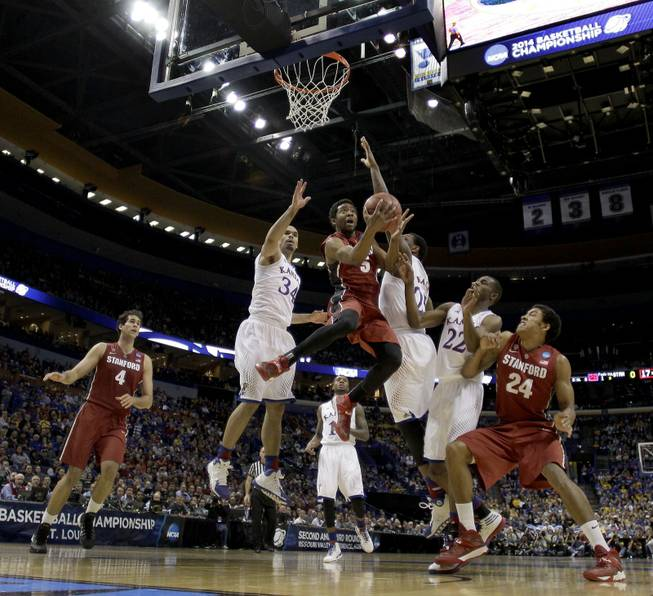 Stanford's Chasson Randle (5) gets between Kansas's Perry Ellis (34) and Tarik Black to shoot during the first half of a third-round game at the NCAA college basketball tournament Sunday, March 23, 2014, in St. Louis.