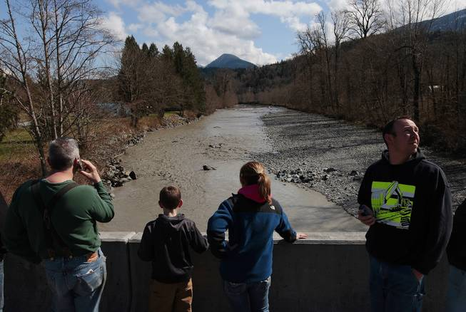 Residents watch as debris comes down the Stillaguamish River from the Whitman Road bridge east of Oso Sunday, March 23, 2014.