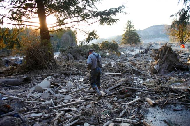 Steve Skaglund walks across the rubble on the east side of Saturday's fatal mudslide near Oso, Wash., Sunday, March 23, 2014.