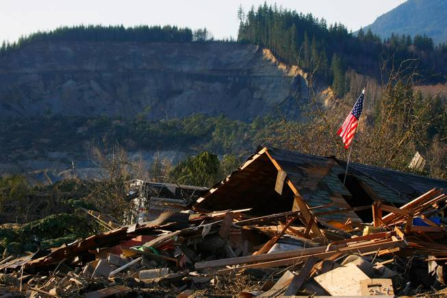 A flag sits atop what was Cory Kuntz and family's home Sunday,  March 23, 2014. The family was at a baseball game Saturday morning when the fatal mudslide swept through the area, destroying everything on their property. The area where the land broke away is seen in the background.