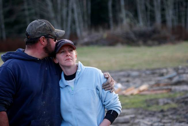 Volunteers Frank and Rhonda Cook watch as the final body they recovered Sunday afternoon is lifted into a helicopter on the east side of Saturday's fatal mudslide near Oso, Wash. The couple started at 6 a.m. searching the area Sunday, March 23, 2014.