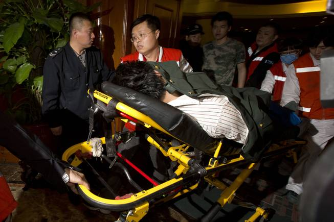 A relative of one of the Chinese passengers aboard the Malaysia Airlines, MH370 is taken away on a stretcher after being told of the latest news in Beijing, China, Monday, March 24, 2014.