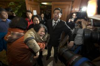 A relative of one of the Chinese passengers aboard the Malaysia Airlines, MH370 collapses in grief after being told of the latest news in Beijing, China, Monday, March 24, 2014.