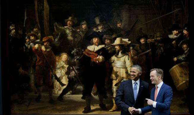 U.S. President Barack Obama, left, and museum director Wim Pijbes pose in front of  Dutch master Rembrandt's The Night Watch painting during a visit to the Rijksmuseum in Amsterdam, Netherlands, Monday, March 24, 2014.