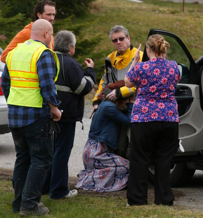 A woman collapses near the Oso Fire Department as neighbors look for news regarding the fatal mudslide that washed over homes and over Highway 530 east of Oso, Wash., Saturday, March 22, 2014. Highway 530 was closed in both directions, and authorities confirmed at least 2 fatalities by Saturday afternoon.