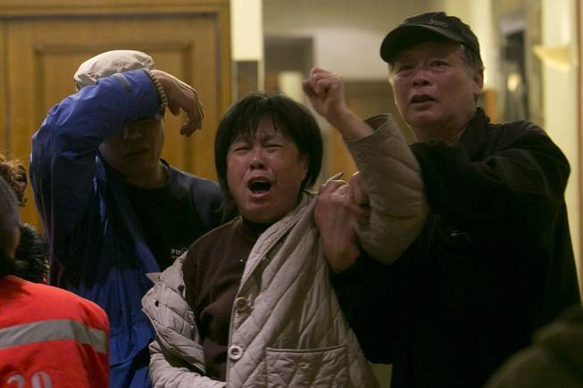 A relative of one of the Chinese passengers aboard missing Malaysia Airlines MH370 grieves after being told of the latest news in Beijing, China, Monday, March 24, 2014. A new analysis of satellite data indicates the missing Malaysia Airlines plane crashed into a remote corner of the Indian Ocean, Malaysian Prime Minister Najib Razak said Monday.