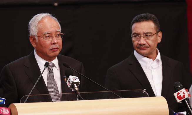 Malaysian Prime Minister Najib Razak, left, and acting transport minister Hishammuddin Hussein speak during the press conference about the missing Malaysia Airlines jet, MH370, at Putra World Trade Centre in Kuala Lumpur, Malaysia, Monday, March 24, 2014. Razak said a new analysis of satellite data indicates the missing plane plunged into a remote corner of the Indian Ocean.