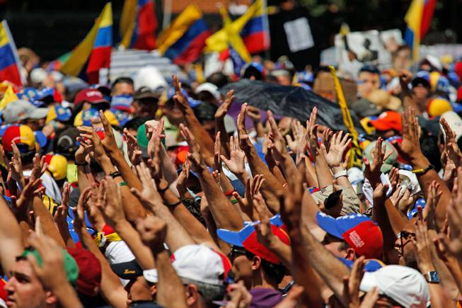 Supporters hold out their hands to greet Carlos Vecchio, the national political coordinator of the Popular Will party, an anti-government group formed by jailed opposition leader Leopoldo Lopez before his arrest, during an anti-government protest in Caracas, Venezuela, on Saturday, March 22, 2014.