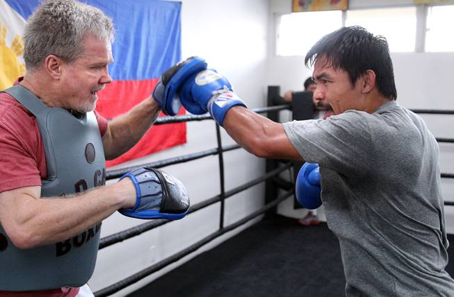 Manny Pacquiao hits the mitts with Hall of Fame trainer Freddie Roach, left, during training Monday, March 24, 2014, for his eagerly-anticipated rematch against undefeated WBO World Welterweight champion Timothy Bradley.