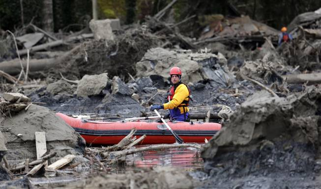 A searcher uses a small boat to look through debris from a deadly mudslide Tuesday, March 25, 2014, in Oso, Wash. At least 14 people were killed in the 1-square-mile slide that hit in a rural area about 55 miles northeast of Seattle on Saturday. Several people also were critically injured, and homes were destroyed.