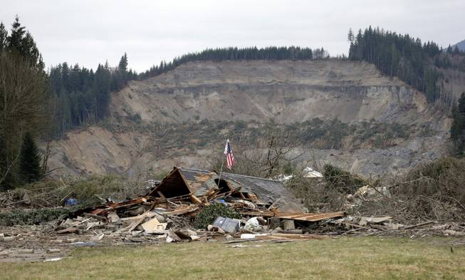 A flag, put up by volunteers helping search the area, stands in the ruins of a home left at the end of a deadly mudslide from the now-barren hillside seen about a mile behind, Tuesday, March 25, 2014, in Oso, Wash. At least 14 people were killed in the 1-square-mile slide that hit in a rural area about 55 miles northeast of Seattle on Saturday. Several people also were critically injured, and homes were destroyed.