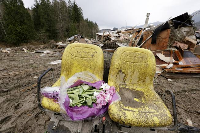 Flowers are left on debris next to a demolished home where a woman's body was found following a deadly mudslide, Tuesday, March 25, 2014, in Arlington, Wash. At least 14 people were killed in the 1-square-mile slide that hit in a rural area about 55 miles northeast of Seattle on Saturday. Several people also were critically injured, and homes were destroyed.