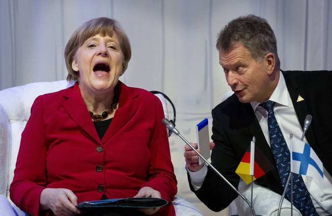German Chancellor Angela Merkel, laughs talking to Finland's President Sauli Niinisto, right, as they attend an informal plenary session on the last day of the Nuclear Security Summit (NSS) in The Hague, Netherlands, Tuesday, March 25, 2014.