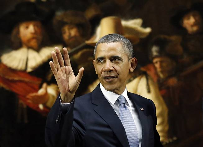 U.S. President Barack Obama waves in front of  Dutch master Rembrandt's The Night Watch painting during a visit to the Rijksmuseum in Amsterdam, Netherlands, Monday, March 24, 2014. Obama will attend the two-day Nuclear Security Summit in The Hague.