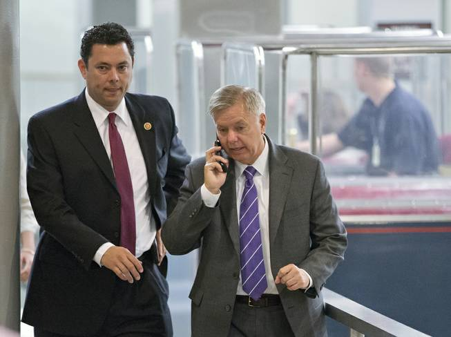 Rep. Jason Chaffetz, R-Utah, left, and Sen. Lindsey Graham, R-S.C., walk together as Graham and other senators head to the floor at the Capitol in Washington, Wednesday, July 10, 2013.