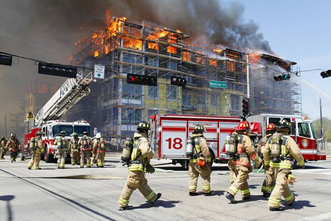 Houston firefighters work to extinguish a five-alarm fire at a construction site Tuesday, March 25, 2014, in Houston. Fire officials said more than 200 emergency personnel were at the scene Tuesday afternoon and were working to protect nearby buildings.