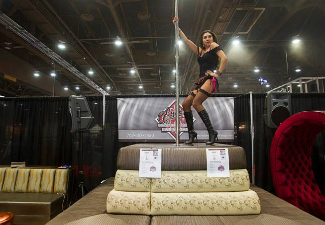 Karen Fujimoto dances at the Encore Upholstery & Design booth during the Nightclub & Bar Convention and Trade Show at the Las Vegas Convention Center Wednesday March 26, 2014.