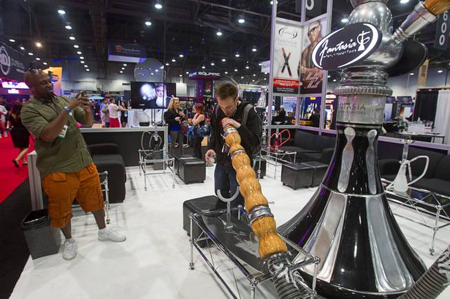 Justin Lawrence of Morgantown, Penn. has his photo taken with a giant hookah during the Nightclub & Bar Convention and Trade Show at the Las Vegas Convention Center Wednesday March 26, 2014.