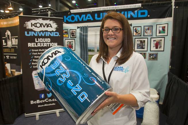 Laura Davis holds an oversized can of Koma Unwind relaxation drink during the Nightclub & Bar Convention and Trade Show at the Las Vegas Convention Center Wednesday March 26, 2014.