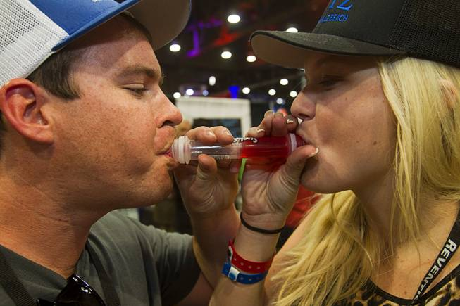 "William Cole and his girlfriend Kelsey Mackenzie try out the ""Suck & Blow"" jello shot during the Nightclub & Bar Convention and Trade Show at the Las Vegas Convention Center Wednesday March 26, 2014."