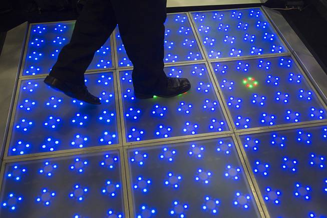 Ozzie Sanchez of Pro Sound and Designs Las Vegas walks over an LED dance floor during the Nightclub & Bar Convention and Trade Show at the Las Vegas Convention Center Wednesday March 26, 2014.
