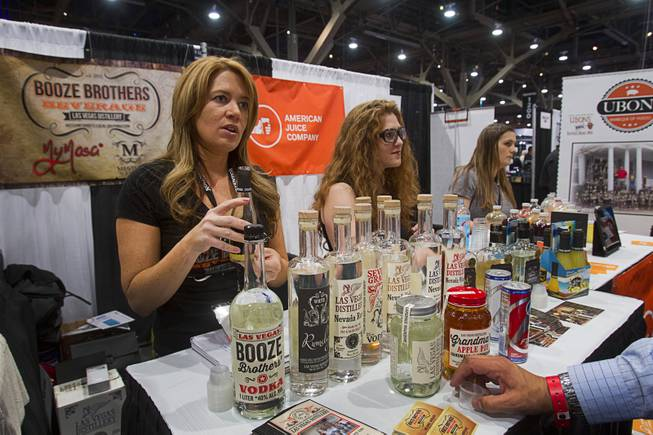Melanie Andrade, left, of Booze Brothers Beverage, shows off local products during the Nightclub & Bar Convention and Trade Show at the Las Vegas Convention Center Wednesday March 26, 2014.