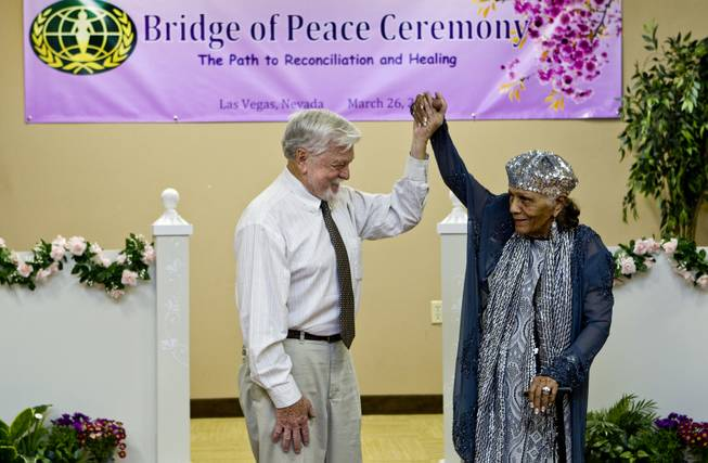 Assemblyman Joseph Hogan and Dr. Sarann Knight Preddy celebrate as they participate in a Bridge of Peace Ceremony of Reconciliation and Healing at the Elks Lodge on Wednesday, March 26, 2014. It was a highlight during A Moulin Rouge Affair sponsored by the Harrison House.