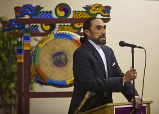Pastor Juan Morales gives the opening prayer for A Moulin Rouge Affair sponsored by the Harrison House at the Elks Lodge on Wednesday, March 26, 2014.