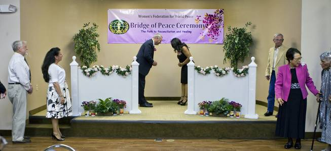 Brian Greenspun bows to Nakia Woodson as they participate in a Bridge of Peace Ceremony of Reconciliation and Healing at the Elks Lodge on Wednesday, March 26, 2014. It was a highlight during A Moulin Rouge Affair sponsored by the Harrison House.