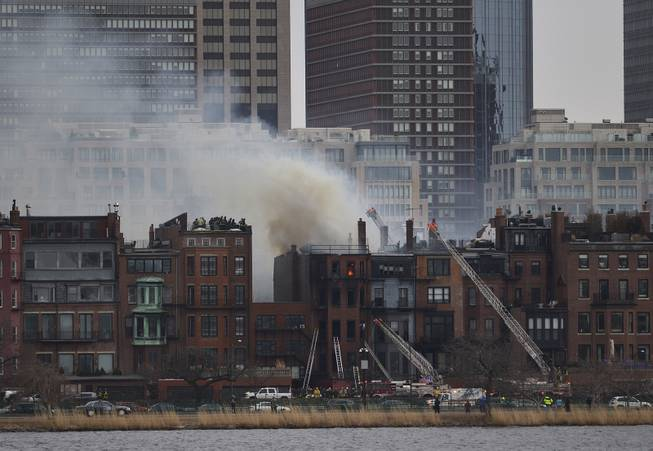 A multi-alarm blaze at a structure is seen from Cambridge, Mass., as firefighters respond, Wednesday, March 26, 2014. A Boston city councilor said two firefighters have died in a fire that ripped through a brownstone.
