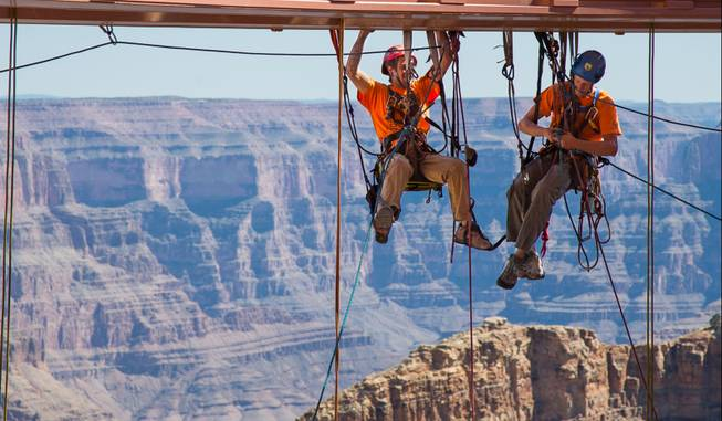 In this Tuesday, March, 25, 2014, photo provided by Abseilon USA via AZ Photos, technicians dangle from a series of ropes before polishing the underside glass at Grand Canyon Skywalk in Hualapai Reservation, Ariz. The more than 40 panes of glass underneath the horseshoe-shaped bridge on the Hualapai reservation aren't easily accessible. The structure juts out 70 feet from the edge of the Grand Canyon, offering visitors a view of the Colorado River 4,000 feet below.