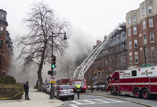 Firefighters fight a multi-alarm fire at a four-story brownstone in the Back Bay neighborhood near the Charles River, Wednesday, March 26, 2014, in Boston. Boston EMS spokesman Nick Martin says four people, including at least three firefighters, have been taken to hospitals.