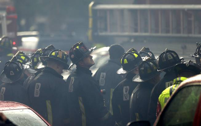 Firefighter look on at the scene of a multi-alarm fire at a four-story brownstone in the Back Bay neighborhood near the Charles River, Wednesday, March 26, 2014, in Boston.