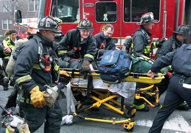 Firefighters scream for an ambulance as they work on and rush an injured firefighter on a stretcher down Beacon Street, Wednesday, March 26, 2014, in Boston. Firefighters responded to a four-story brownstone fire. A Boston city councilor said two firefighters have died in the fire.