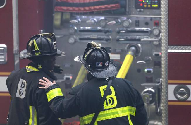 A firefighter places his hand on the shoulder of another at the scene of a multi-alarm fire at a four-story brownstone in the Back Bay neighborhood near the Charles River, Wednesday, March 26, 2014 in Boston.