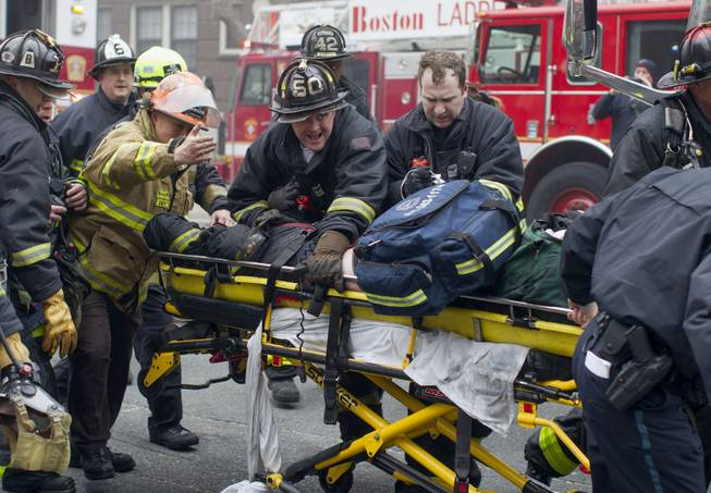 Firefighters and emergency medical personnel rush a firefighter from the scene of a multi-alarm fire at a four-story brownstone in the Back Bay neighborhood near the Charles River, Wednesday, March 26, 2014, in Boston. Boston EMS spokesman Nick Martin says four people, including at least three firefighters, have been taken to hospitals.