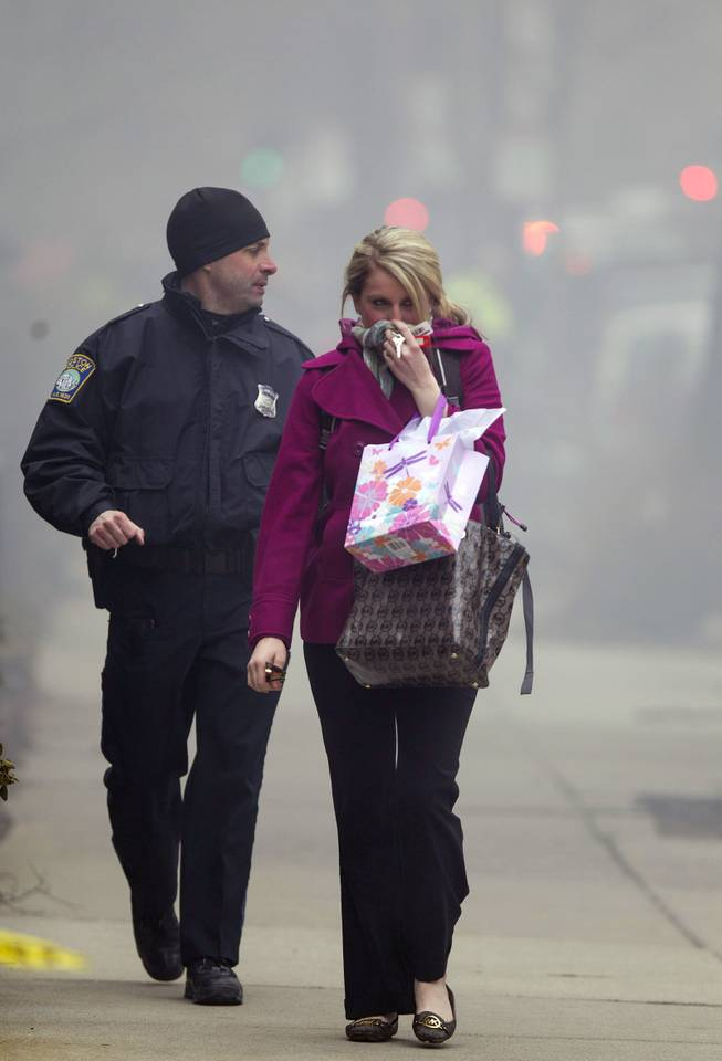A Boston Police officer escorts a woman away from the scene of a multi-alarm fire at a four-story brownstone in the Back Bay neighborhood near the Charles River, Wednesday, March 26, 2014, in Boston. Boston EMS spokesman Nick Martin says four people, including at least three firefighters, have been taken to hospitals.