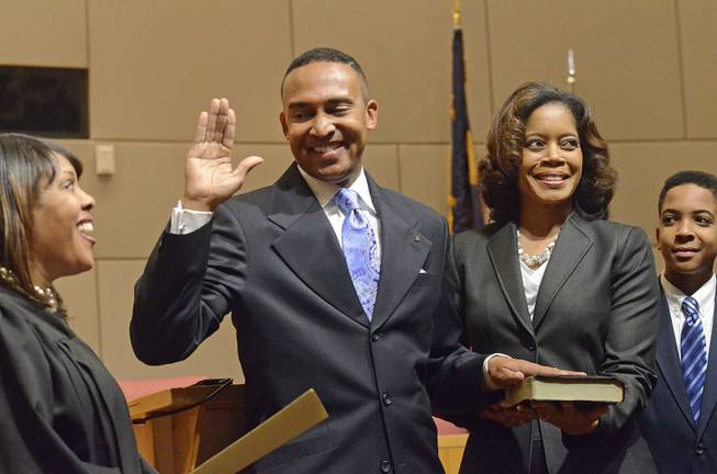 Mecklenburg County District Judge Tyyawdi Hands, left, administers the oath of office to Patrick Cannon as Charlotte's new mayor, with his wife, Trenna, and son Patrick, next to him, at the Charlotte Government Center, in Charlotte, N.C., Dec. 2, 2013.
